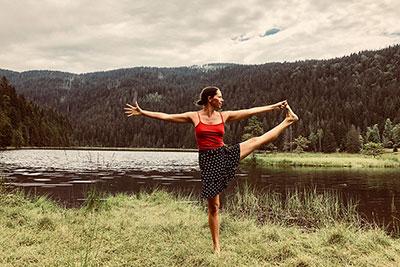 Nana Merz von Yoga Jetzt in einer Einbeinstandhaltung vor Naturkulisse am See